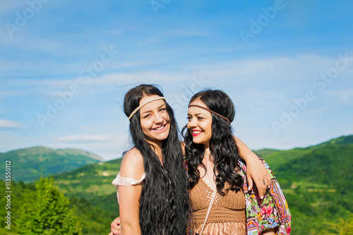 Poster Two beautiful boho sisters hugging outdoors on sunny summer day