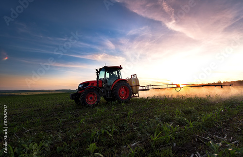 Poster Tractor spraying a field on farm in spring, agriculture