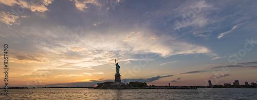 Foto op Aluminium New York dramatic panorama of Statue of Liberty during sunset