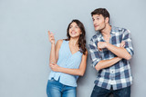 Smiling couple standing and pointing at something over gray background