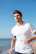 Attractive young sportsman jogging on the beach