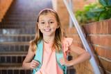Smiling schoolgirl standing on staircase