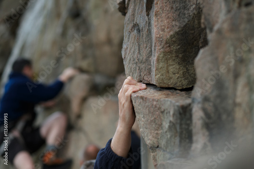 Poster Hand of male rock climber clings to a cliff