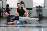 Man With Personal Trainer On Bosu Abs Exercise