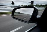 Specchietto retrovisore laterale di una macchina che viaggia in autostrada