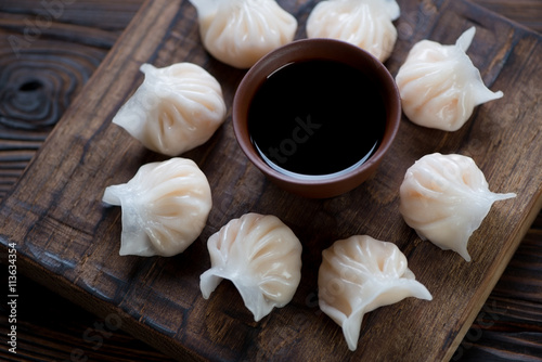 Poster Rustic wooden serving board with steamed dim sums, closeup