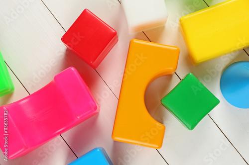 Colorful  children's building blocks on white wooden background © Africa Studio