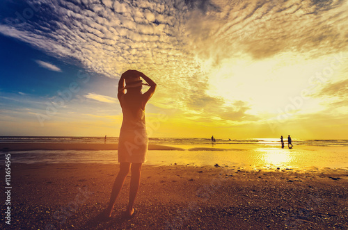 Foto op Aluminium Strand young woman standing on sand and looking to a sky