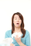 middle aged woman with an allergy sneezing into tissue