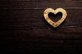 Golden heart over dark-brown wooden background - 113692348