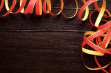 Party/carnival background - colorful paper streamers over dark brown wooden background - 113692594
