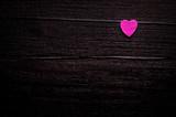 Little pink heart over dark-brown wooden background - 113692715