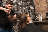 Hairdresser during work with beautiful woman