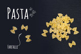 Uncooked Italian pasta Farfalle on black slate stone background with white lettering, top view