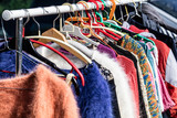 colored second hand women's sweaters at flea market - 113729316