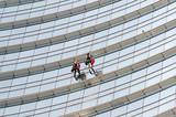 Uomini che lavano i vetri di un grattacelo a Milano