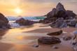 Fantastic big rocks and ocean waves at golden sundown