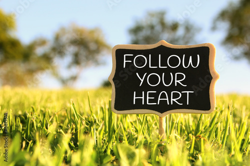Wooden chalkboard sign with quote: FOLLOW YOUR HEART Poster