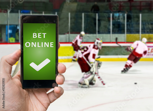 Man is watching ico hockey and is betting online via smartphone. Poster