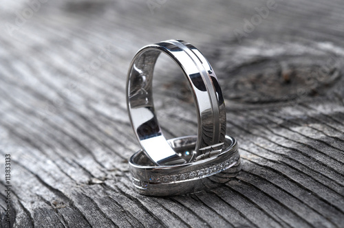 obraz lub plakat Two wedding rings on rustic wood, b&w