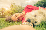 Young girl taking a selfie with her dog lying on the grass at the park