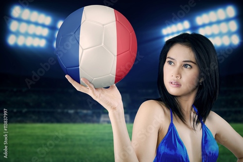 Poster Sexy model holds a soccer ball in stadium