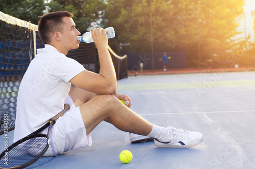 Poster Young tennis player drinking water after playing, sitting on court and looking a