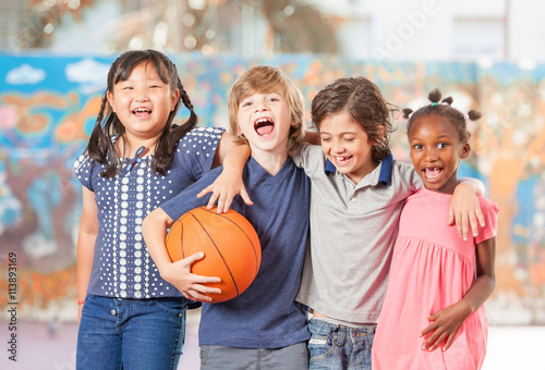 Fotobehang Basketbal Elementary school children happy playing basketball at school