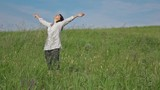 Slow motion video - woman relaxing on a green lawn looking at the sun. Full HD stock footage clip.