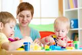woman teaches children handcraft at kindergarten or playschool