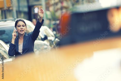 Zdjęcia na płótnie, fototapety, obrazy : New York City Woman on Cell Phone Hailing a Yellow Taxi Cab