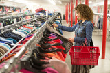 Female browsing through clothing In a Thrift Store  - 113910579