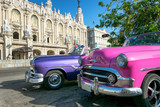 Two colorful vintage taxis and the Great Theater on the background in Havana, Cuba