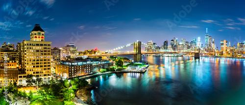 New York City panorama by night. Brooklyn Bridge spans East River linking Manhattan and Brooklyn boroughs