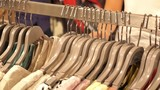 Woman in Clothing Store Choosing Clothes on Hangers Closeup