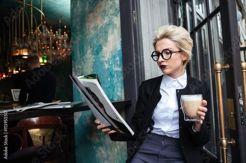 Close-up portrait d'une jeune fille assise dans le café avec le magazine Poster