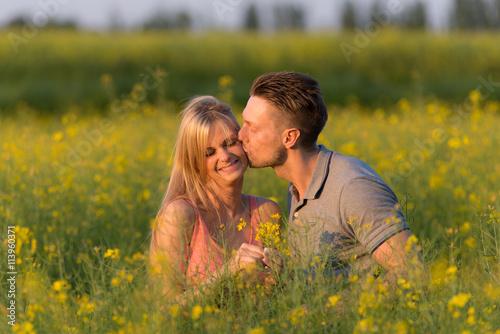 Zdjęcia na płótnie, fototapety, obrazy : mann gibt seiner frau einen kuss im rapsfeld