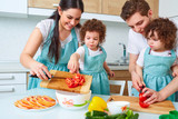 Happy family with twin daughters in the kitchen. Cheerful mother