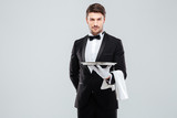 Fototapety Handsome yong waiter in tuxedo and gloves holding empty tray