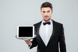 Butler in tuxedo holding blank screen tablet on tray