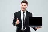 Cheerful businessman holding blank screen laptop and showing thumbs up