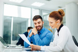 Young business people look at paper document
