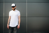 Hipster wearing white blank t-shirt and a baseball cap with spac