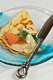Savory Crepes with smoked salmon, sour cream, and dill on a blue plate with knife