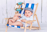 Funny little toddler sitting on the deckchair
