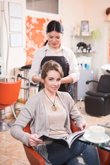 Beautiful lady having her hair cut or done in hairdressing saloon. Pretty lady reading magazine in beauty saloon.