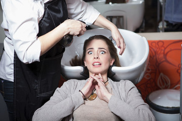 Portrair of frightened beautiful lady while having her hair wash in hairdressing saloon. Pretty lady looking at camera.