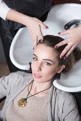 Hairdresser washing hair of beautiful lady in hairdressing saloon. Client having her hair wash by barber girl.