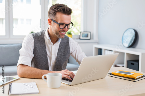 Young happy designer working on laptop from home - freelance con