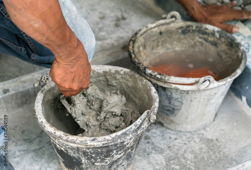cement portland gray fresh mortar mix with spatula tool in bucket Poster